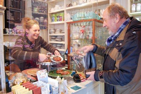 SOM PÅ 50-TALLET: - Jeg tar gjerne en kanelbolle, takk, sier Tomm Ivar Svensen til Cecilie Steensen Skovholt, vertinnen på Svartskog Kolonial. Innredningen er helt lik den gang Svensen handlet i landhandleriet her på 50-tallet.