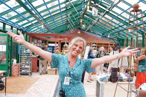 ENTUSIASTISK: Daglig leder for Rammestiftelsen, Mia Kron, ønsker velkommen til nyåpnede Ramme gård. Hun står i Diversen kafé og gårdsbutikk i en hyggelig atmosfære blant kafegjester,planter og salgsgjenstander.