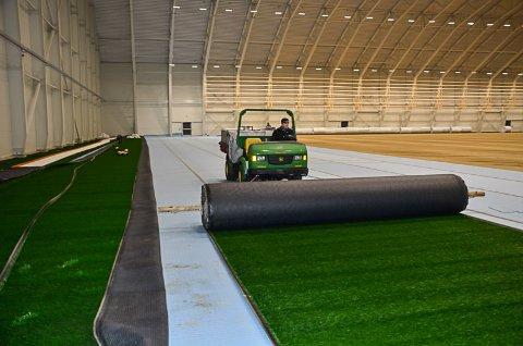 PÅ GANG: Tirsdag startet arbeidet med å legge kunstgresset i de nye fotballhallen. Arbeidet tar cirka ei uke. Foto: Trond Isaksen