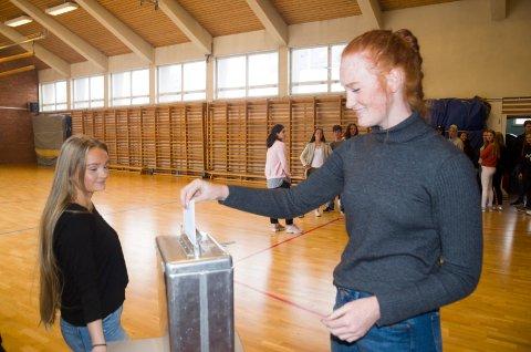 Gina Engen stemmer ved skolevalget ved Ringerike videregående skole. Valgfunksjonær Martine Schulerud Nilsen passer på at alt går rett for seg.