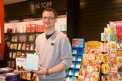 ROMANER: Anton Wasa, butikksjef på Norli på Kuben, viser fram to av de romanene som har solgt best i førjulstiden, nemlig Søsterklokkene av Lars Mytting og Det innerste rommet av Jørn Lier Horst.