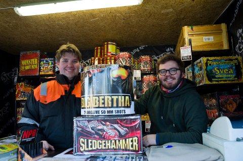 SELGER MYE: Trond Simen Solli Blikken og Aleksander Nysveen med to av fyrverkeripakkene som det selges mye av hos utsalget ved YX 7-eleven i Dalsbråten.