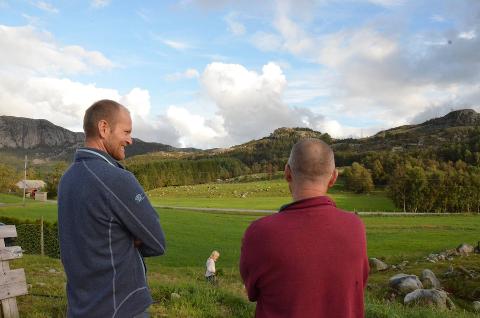 SKEPTISKE: Naboene Øyvind Skjervik (42) og Lars Terje Fjelde (56) står og ser ut over åssidene som kanskje vil være kledd av vindmøller om noen år.