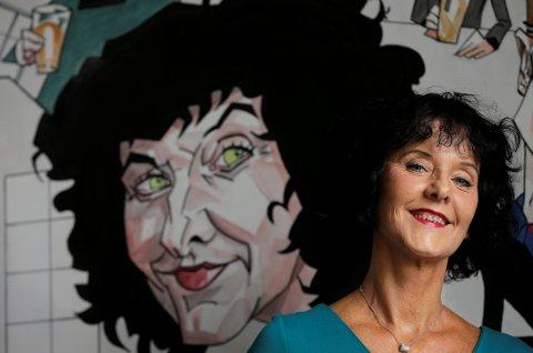 Forfatter Unni Lindell kommer med to nye bøker i høst. Her står hun foran portrettet av seg selv som Steffen Kværnland har tegnet.