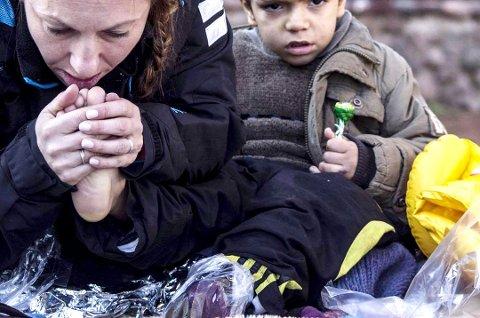 En liten gutt fra Syria blir varmet på stranden av Kristina Quintano etter overfarten mellom Tyrkia og Lesvos.