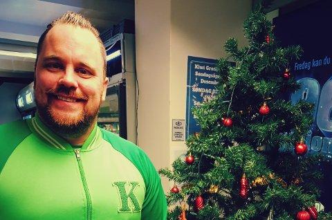 GIVERGLEDE: Butikksjef Klas Arild Roksvaag ved Kiwi i Grønligata har satt opp handlevogn hvor kundene kan donere varer, i tillegg til en juletre hvor de kan legge igjen gaver, til de som ikke har så mye fra før av.