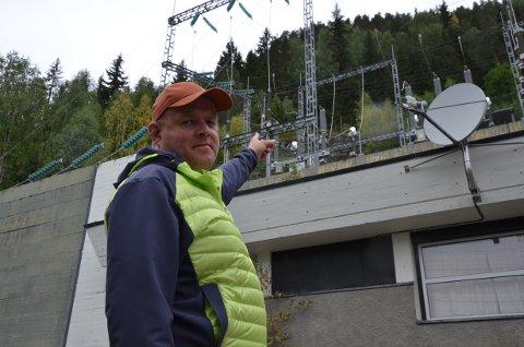 Leif Erik Thorsrud peker  på området overfor kraftstasjonen i Bagn, dit han måtte klatre opp for å slukke flammene han så fra bilen. Foto: Ingrid Ødegård
