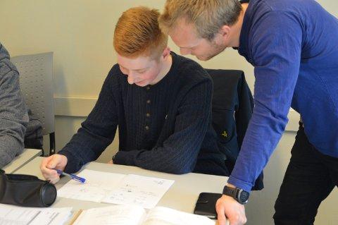 HJELP MED ALT: - Markus Medaas (15) får hjelp med ei matteoppgåve av mentor Johannes Skibeli Herrem (25).