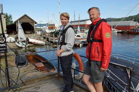Båter gjøres klar i bakgrunnen, mens Theodor Eide (18) fra Redningsselskapet Ung holder kontrollen på land. Her sammen med  Redningsselskapets Dag Kjetil Tufte (t.h.) (Foto: TOM R. HJERTHOLM)