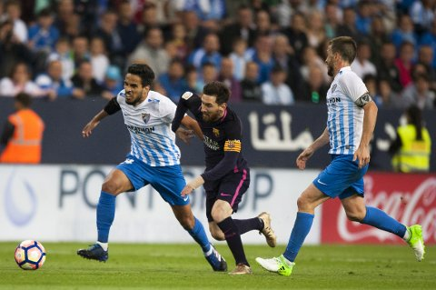 FC Barcelona's Lionel Messi from Argentina , center, duels for the ball against CF Malaga's Recio, left, and Ignacio Camacho, during a Spanish La Liga soccer match between Malaga and Barcelona in Malaga, Spain, Saturday April 8, 2017. (AP Photo/Daniel Tejedor)