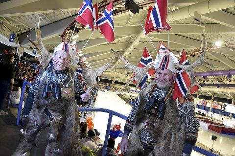 Med gevir fra selvskutt elg, varseltrekant, flagg, kubjeller, spesialkomponerte «kikkerter» og elgskinn gjør de norske skøytesupporterne seg godt bemerket overalt hvor de reiser. Arild Borgen (til venstre) og Rolf Horni er to av dem. Foto: Einar Lundsør