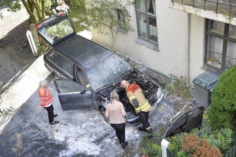 Bileieren og en fra brannvesenet undersøker bilen som brant i Zinken Hopps gate mandag.