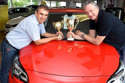 POKALKARA: Mustafa Aset (til v.) og Ivar Skretteberg eier halvparten hver av Hokksund Auto. Her viser de fram de fine pokalene fra Opel Norge.
