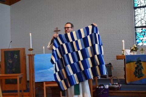 NYTT I DISTRIKTET: Søndag arrangerte Mjøndalen kirke strikkegudstjeneste for andre gang. Kirkerommet var pyntet med strikkede genser og garnnøster. Plaggene kirkegjengerne strikker, som dette pleddet, går til kreftsyke mennesker. – På den måten er det virkelig en gudstjeneste med mening, sier prest Arnstein Hardang.