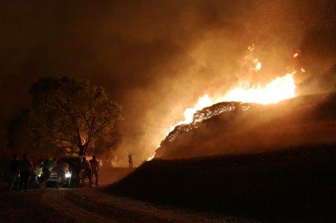 Folk dyttar ein bil som stod fast medan den bragte vatn til dei frivillige brannmennene som kjempa mot flammane nær Obidos, Portugal, i morgontimane måndag 16. oktober.