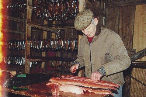 Sild og Villaks:  Per Magnussen filiterer og gjer klar eit par villaks for røyking. I bakgrunnen heng flekt sild langs vegger og i tak, tørka og røykt, klar for sal og konsum. Dette var eit fag han kunne –  bokstaveleg tala til fingerspissane.