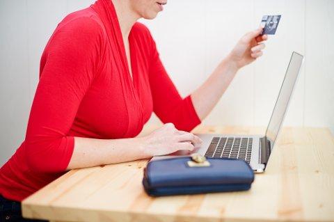 En kvinne betaler en nettbestilling med sitt kredittkort. Rød genser. Sitter foran PC. Netthandel. Shopping på nettet. (Foto: Robert Schlesinger / NTB scanpix)
