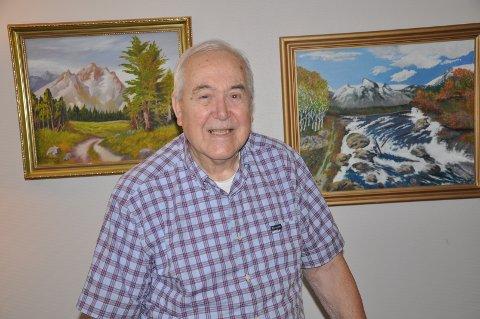 Fritz Simonsen med bilder han selv har malt, som henger på veggen.