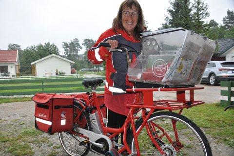 """POSTEN SKAL FRAM: Hilde G. Larsen har slitt ut flere sykler etter 37 år som postbud. Her med den nyeste """"doningen"""", som brukes i all slags vær, sommer som vinter."""