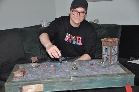 STOR INTERESSE: Henrik med brettspillet Dungeons & Dragons foran seg. Spillbrettet, brikker og gjenstander han han selv laget.