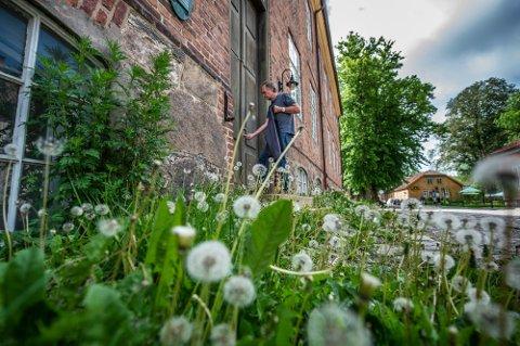 TOM KASERNE: Inngangsdøren til kasernebygget er blass,  den kan trenge et malingstrøk. Her låser festningsforvalter Morten Kjølbo seg inn i bygget han håper skal fylles med liv i nærmeste fremtid. Foto: Geir A.Carlsson