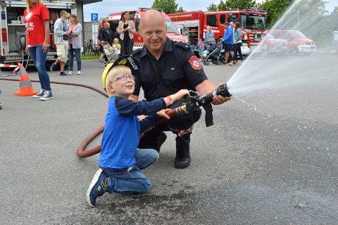 Brannvesenet er som vanlig på plass på Barnas Aktivitetsdag 7. august. Her er Jakob Wich (da 4 år) fotografert da han traff ball med vannstråle med assistanse av Bjørn Magnussen i 2017.