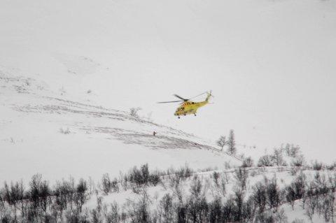 Lyngen  20170316. Et ambulansehelikopter går inn for landing ved stedet der to personer ple tatt av et snøskred i Lyngen i Troms torsdag. Foto: Geir Martin Koch / NTB scanpix