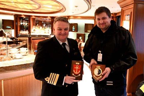 GAVE: Det er tradisjon å dele ut en krest, en plakett med byvåpnet, når nye cruiseskip ankommer Narvik havn.  Narvik havn får en plakett i gave fra skipet. Her er kaptein Alan Hawkin og trafikkinspektør Fredrik Holtet Lien.