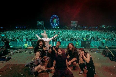 Leo Moracchioli (i midten bak), kona Stine Vea Moracchioli (helt til høyre), svoger Anders Oftedal (i kanindrakten) og resten av Frog Leap poserer foran et ellevilt folkehav etter konserten på Nova Rock i Østerrike sommeren 2019.