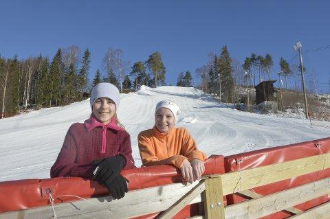 Elevrådsleder Emma Constanse Johansen (12) (t.h.) og elevrådsrepresentant Helene Giske Ødegård Moen (12) er glade for de mange tilbudene de har ved skolen. Her med en nypreppet Pinnikbakken i bakgrunnen.