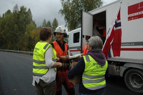 Oppmuntringstilsynet møtte opp med flagg, is og gaver til asfaltleggerne. Her oppmuntrinsagentene Kari Korsmo (til høyre) og Ellen Sagengen i møte med bas for lag nord.