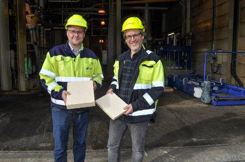 Fabrikkdirektør Kjell Arve Kure (til venstre) og Dag Molteberg viser fram en prøve på de fiberplatene man håper skal bli et nytt og viktig ben å stå på for Saugbrugs. (Arkivfoto: Øivind Kvitnes)