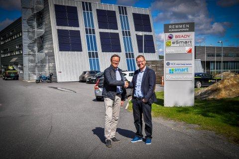 INNGÅR AVTALE: Olympiatoppens Jarle Aambø (t.v) og Smart Innovation Norways Ole Gabrielsen gir hverandre hånden på at de skal hjelpe hverandre i tiden framover. I bakgrunnen er kunnskapssenteret på Remmen sett fra den siden som vender bort fra Høgskolen i Østfold.