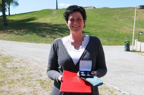 STOLT OG VEMODIG: Solveig Eriksen med medalje og diplomet som hun mottok av Magne Rannestad for farens tjeneste. Hun hadde selv tatt med uniformslua hans til seremonien. Foto: ANDERS SVENDSEN