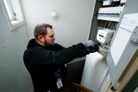 Montør Tim Alexander Refsnes setter inn en automatisk måler i sikringsskapet.