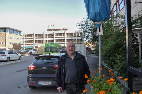 IKKE LOV: Det er ikke tillatt å parkere på parkeringsplassene bak Tommy Hæggernæs på grunn av at det er satt en pose over P-skiltet. Hæggernæs mener likevel at det burde ha kommet klarere fram at parkeringen ikke gjelder her.