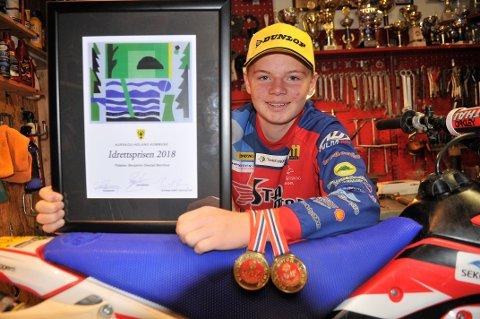 I POSE OG SEKK: Benjamin Glestad Bernhus viser stolt fram høstens «fangst» som MC-utøver. Diplomet som forteller at han er en av to vinnere av Aurskog-Hølands idrettspris 2018, samt gullmedaljer, både fra i år og fjor som NMK-mester i enduro i  ungdomsklassen.