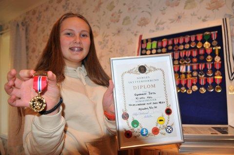NORGESMESTER: Synnøve Berg med bevisene som forteller om hennes første norgesmesterskap i skyting; Gullmedalje og diplom etter at hun vant ungdomsklassen i årets NM i miniatyrskyting 50 meter.