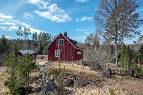 Det røde, lille huset ligger i en lysning i skogen.
