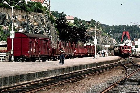Jernbaneperrongen i Kragerø 1980: En gang hadde Kragerø en jernbane. Den ble innviet i 1927 og lagt ned i 1988. Dette fotografiet viser den røde motorvognen som kommer kjørende inn mot jernbanestasjonen. Motorvognen trafikkerte strekningen Neslandsvatn – Kragerø. Alt dette er nå borte og erstattet med vei. I bakgrunnen sees den store bukkrana til Tangen Verft. Også den og skipsverftet er borte. Med jernbanen og Tangen Verft forsvant mange viktige arbeidsplasser fra Kragerø.