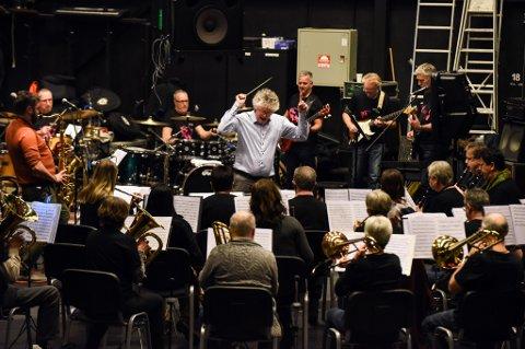 ØVING: Clive Andersen står i sentrum for både korps og rockeband og dirigerer med heile seg. Bildet er frå torsdag kveld då rockebandet og musikklaget hadde fellesøving.