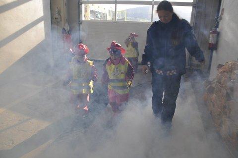 RØYK: Her tar varabrannsjef Sara Johansson ungene med inn i den ufarlige røyken.