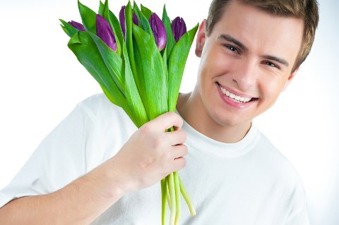 handsome young man with a bouquet of tulips