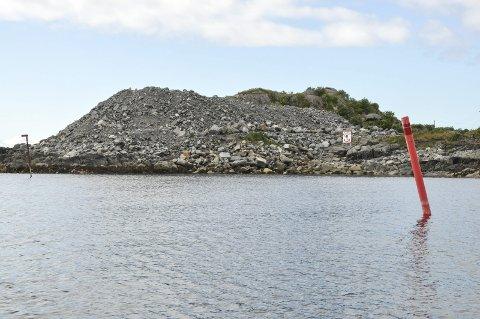 Fylling: Steinmassene ligger klare på Buøya. Moloen ble påbegynt i 2011, men ikke fullført. Det ligger dermed en bunnfylling ut til den røde flytestaken t.h. i bildet. En fylling båtfolk og fiskere utgjør en fare. Foto: Lise Fagerbakk