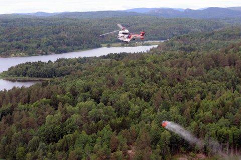 Skogbrannhelikopter, Super Puma, med bøtte i lufta.