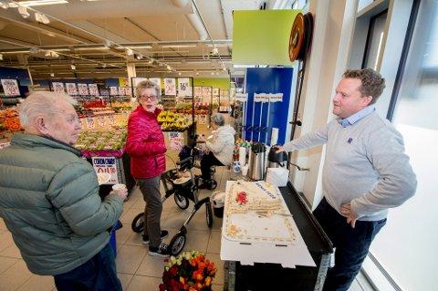 KAFFE OG KAKER TIL ALLE: Butikksjef Tor Egil Skamsar bød på kake og kaffe til alle kundene som stakk innom mandag formiddag. Her tar han seg en prat med to av butikkens faste kunder, Laila og Cato Berg.