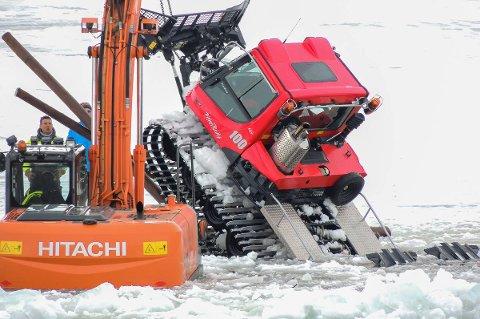BERGES OPP: Tråkkemaskinen ble til slutt hentet opp fra vannet etter at den gikk gjennom isen i Karasjok mandag. Foto: Kjell Harald Sæther