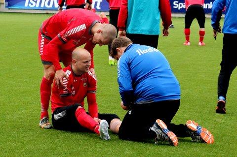 Hans Eriksen Norbye nede for telling under onsdagens TIL-trening på Alfheim. Her får han behandling av fysioterapeut Einar Hauglid, og litt moralsk støtte fra Zdenek Ondrasek.