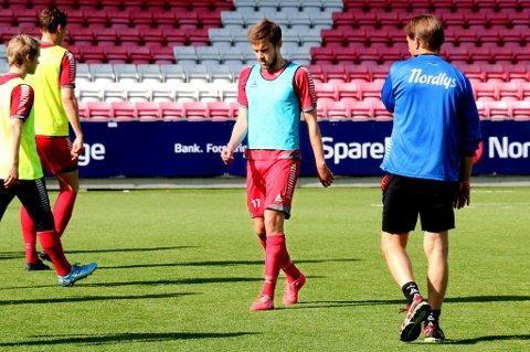 Remi Johansen går forbi trener Steinar Nilsen under tirsdagens TIL-trening på Alfheim. 24-åringen tror ikke det er verken småbarnsliv eller kontraktforhold som har sendt ham på benken, men derimot en slapp forestilling mot Strømsgodset.