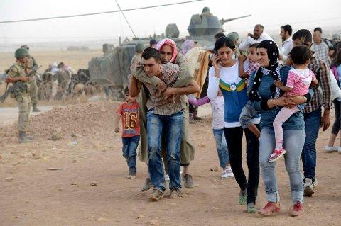 FLUKT:Bildet viser flyktinger fra Syria som krysser over grensen til Tyrkia. (Foto: STRINGER/TURKEY)